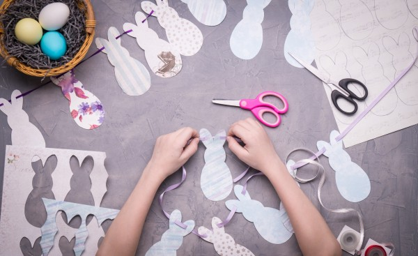 Preparation Of Decor For Easter: The Girl Collects A Garland On A Ribbon Of Paper Rabbits.