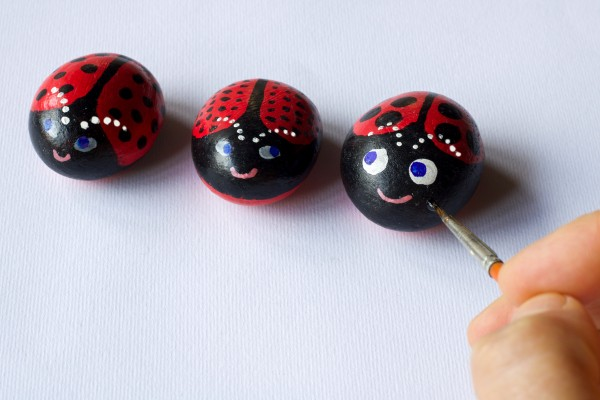 Hand Painting Three Stones As Cute Ladybugs On White Paper