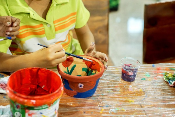 Child Wear Green Polo Shirt Study And Learning Paint On Flower Pot In The Art Classroom.
