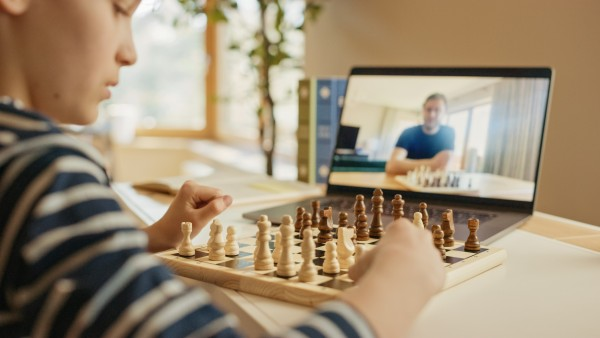 Brilliant Little Boy Playing Chess With His Distant Relative Or Uncle, Uses Laptop For Video Call. Remote Online Education, E Education, Communication With Family, Homeschooling.